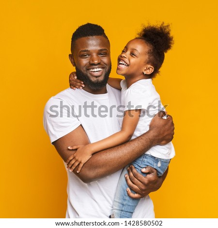 Happy african man embracing his positive little daughter, orange studio background