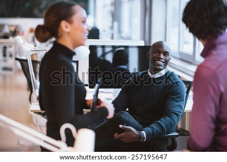 Happy african man sitting at desk with coworkers smiling. Young business executives during break.