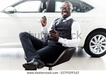 Happy African man sitting on a chair in front of a new car
