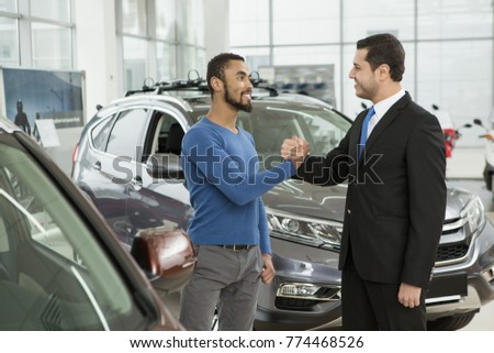 Happy African man smiling shaking hands with a professional car salesman at the dealership copyspace happiness positivity partnership contract deal selling buying business vehicle transportation #774468526