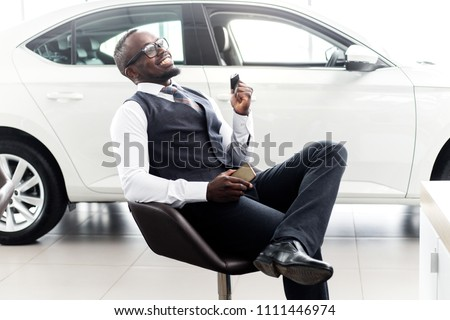 Happy African man with keys in his hands happy buying a new car sitting on a chair in the showroom