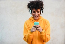 Happy african millennial guy listening music playlist with smartphone app outdoor - Young man having fun with technology trends - Tech, generation z and stylish concept - Focus on face