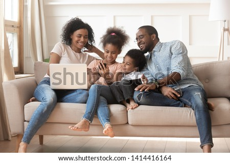 Happy african parents and kids obsessed addicted to gadgets use laptops digital tablet phone sit on sofa, black family mom dad and children have fun with devices at home internet technology addiction