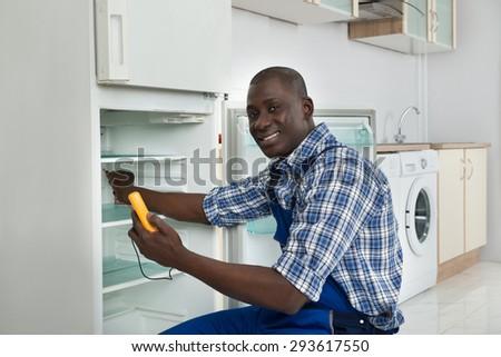 Happy African Technician Repairing Refrigerator Appliance In Kitchen Room