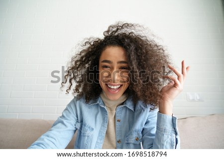 Happy african teen girl blogger talking to camera video calling, recording vlog. Happy afro young woman laughing distance chatting at home office. Funny social media influencer streaming. Webcam view