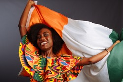 Happy african woman in national clothes smiling and posing with a flag Ivory Coast, C te d'Ivoire isolated over a gray background
