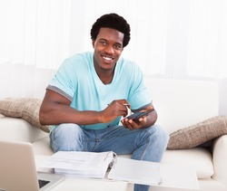 Happy African Young Man Calculating His Finance Expenses At Home