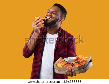 Happy African Young Man Enjoying Pizza Biting Tasty Slice Posing With Box Over Yellow Background. Junk Food Lover Eating Italian Pizza In Studio. Unhealthy Male Nutrition And Cheat Meal