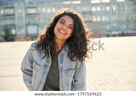 Happy African young woman wearing denim jacket laughing looking at camera standing on street. Smiling Afro American teen generation z hipster girl posing outdoor backlit with sunlight, portrait.