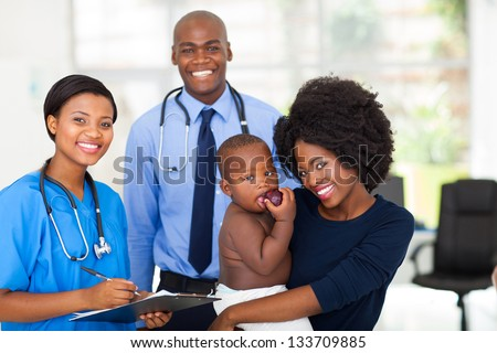 happy afro american mother holding her baby boy after checkup with nurse and doctor