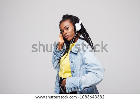 Happy afro american woman with afro and casual clothing dancing to the music she is listening to on her phone