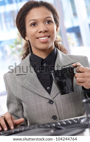 Happy afro businesswoman using computer, drinking coffee, smiling.