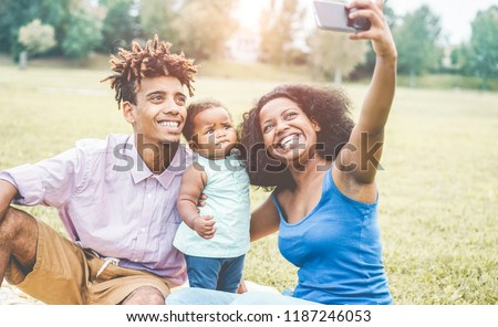 Happy afro family making video story for social network app with new smartphone - African young parents and their daughter having fun with new trends technology - Love concept - Focus on adult faces #1187246053