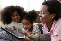 Happy afro family. Smiling African American mother with two little daughter looking at the digital tablet while lying on sofa at home. people, family, technology and education concept
