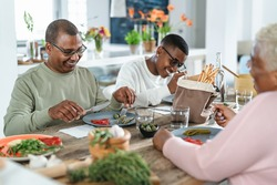 Happy afro Latin family eating healthy lunch with fresh vegetables at home - Food and parents unity concept