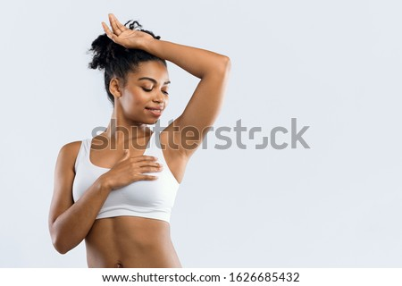 Happy afro woman smelling her fresh armpit over grey background, putting hand up, copy space, advertisement for under arm deodorant Сток-фото ©