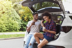 Happy afrocouple sitting in open car back, having stop off, drinking coffee. Romantic traveling concept