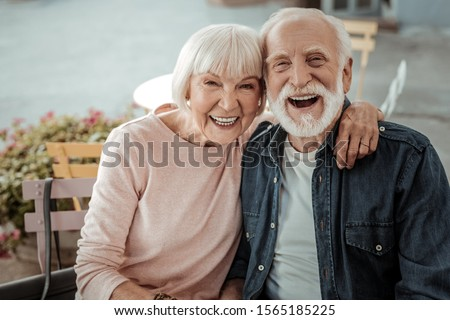 Happy aged couple. Positive aged woman sitting with her husband while hugging him