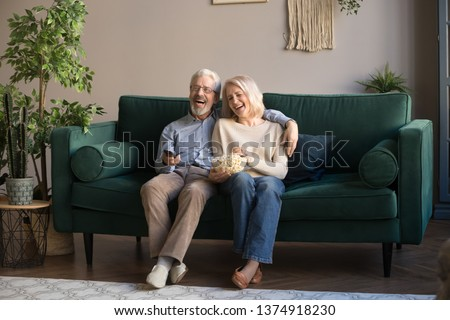 Happy aged couple, wife and husband watching tv, comedy movie and eating popcorn snack, laughing, sitting on cozy couch at home, mature family, man and woman enjoying free time, weekend together