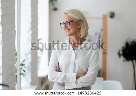 Happy aged grey-haired businesswoman wearing glasses stand with arms crossed look in distance dreaming or visualizing, smiling senior woman worker plan think of success. Business vision concept