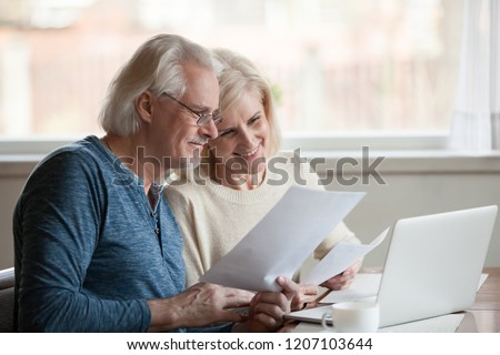 Happy aged husband and wife hold papers using laptop for online banking, satisfied senior couple smiling checking utility bills or insurance at computer with easy access, elderly users of technology