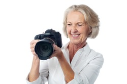 Happy aged woman viewing her photos in DSLR camera