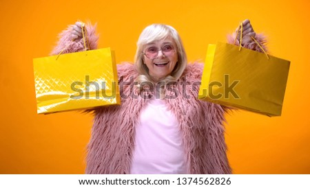 Happy aging lady in funny pink coat showing yellow shopping bags, wasting money
