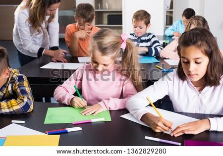 happy american  children of elementary age having class of art