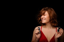Happy American Girl with a perfect hairstyle and make-up is posing with casino chips in her hands. Casino, Poker and Roulette. Gambling, young rye-haired Woman Lucky casino winnings. isolated. smile
