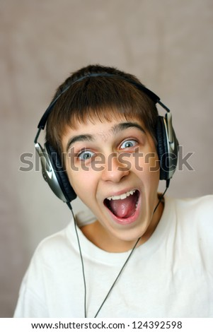 Happy and Amazed Teenager in Headphones Listening to the Music - stock photo