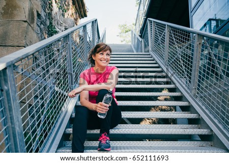 Happy and beautiful middle aged woman sitting on metallic stairs relaxing before running outdoors holding a water bottle