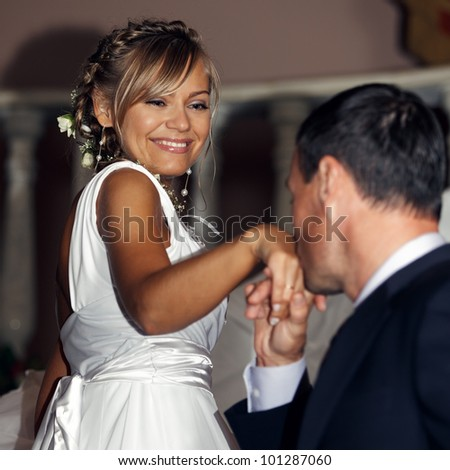 Happy and beautiful newlyweds. Groom kissing brides hand