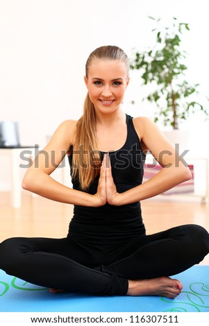 Happy and beautiful woman meditate at home on blue mat