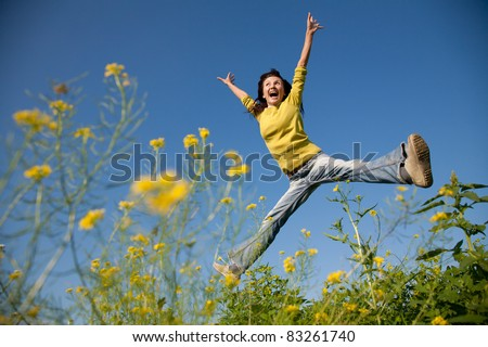 Happy and beautiful young girl jumping high in a summer field