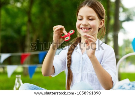 Happy and carefree girl in white cotton blouse playing with fidget spinner in park on summer day