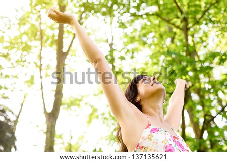 Happy and carefree woman raising arms  to the sky on fresh bright spring greenery. Caucasian beautiful girl happiness and relaxation on nature.