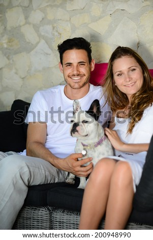 happy and cheerful young couple man woman with pet dog french bulldog sitting outdoor in sofa