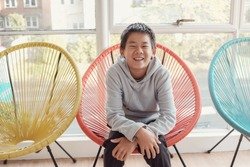 Happy and confident tween mixed race multiethnic Asian boy smiling and sitting on colorful red chair, preteen portrait