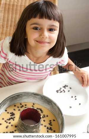 Happy and cute little girl pouring chocolate chips to cake