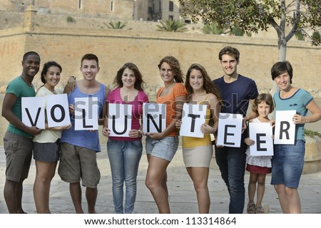 happy and diverse volunteer group holding sign