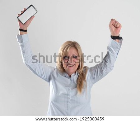 happy and exalted woman with raised hands holding phone in hand Foto stock ©