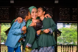 Happy and excited children with an envelope of pocket money or raya angpao are kissing their mother during Eid al-Fitr celebration. Malaysian Family and Raya Concept.