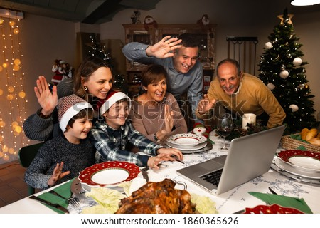 Happy and Excited family greeting their family and friends on Christmas eve using a skype video call during the coronavirus pandemic. Some relatives waving and talking to a laptop. Social distancing.