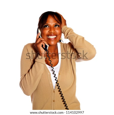 Happy and excited female conversing on phone against white background