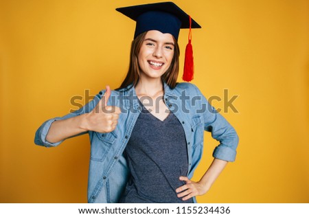 Happy and excited young beautiful student girl with hat of graduation on head isolated on yellow background with thumb up