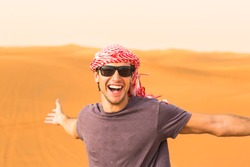 Happy and excited young male tourist standing with arms stretched against the golden Arabian desert sand dunes in the background.