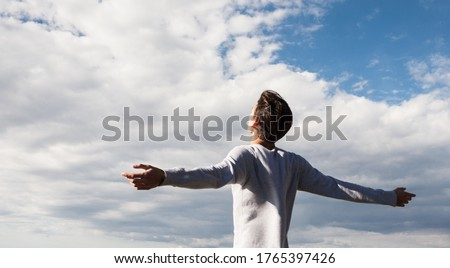 Happy and free young male person with open arms towards the blue sky. Feeling good and freedom. Foto stock ©