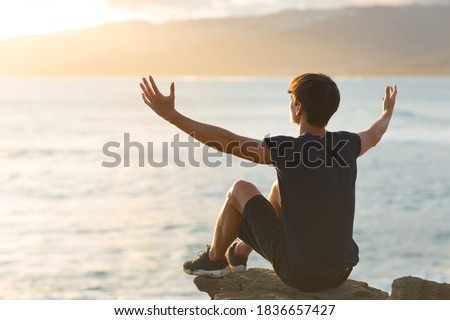 Happy and free young man sitting on top of a cliff facing the ocean view and raising arms up to the sky. Feeling joyful. Stockfoto ©