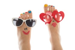 Happy and funny caucasian summer feet with colorful nail polish and sunglasses