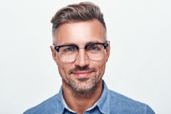 Happy and handsome. Close up portrait of charming bearded man in eyewear looking at camera and smiling while standing against grey background